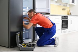 Appliance repair technician from one click appliance services fixing a broken appliance in Vancouver, BC.